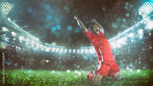 Cuadros en Lienzo Soccer striker in red uniform rejoices for the victory at the stadium