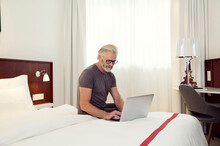 A Man Sitting On A Bed Working...