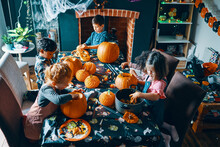 4 Children Around A Table Emptying The Middle Out Of Pumpkins.