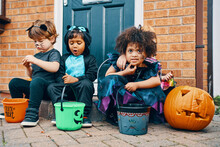 Three Children Dressed For Halloween Sitting On A Doorstep Eating Sweets.