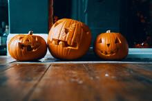 Three Pumpkin Heads On A Hearth.