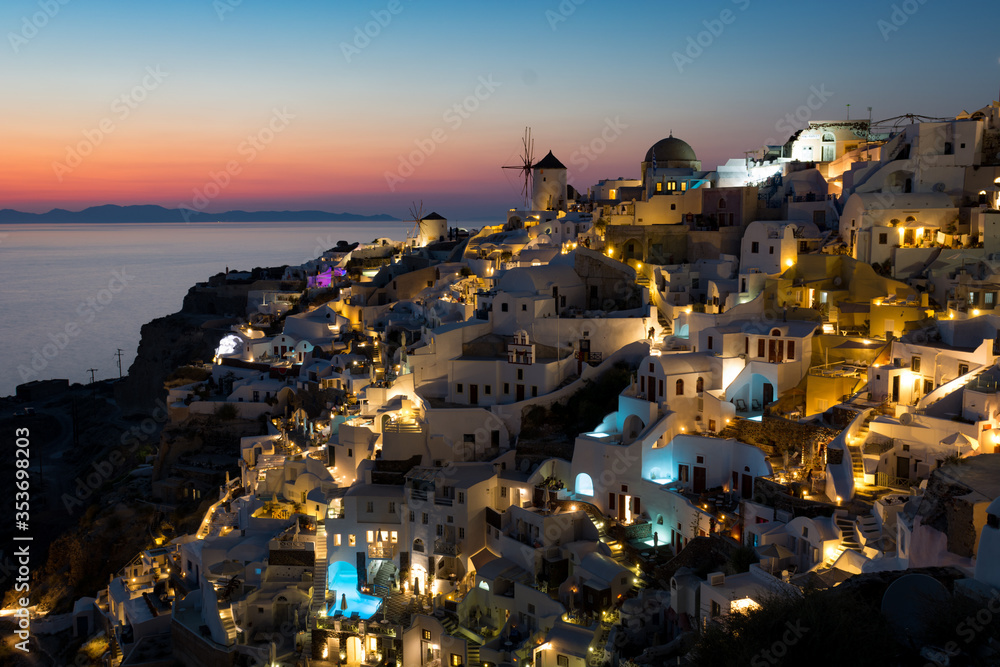 Fototapeta Sunset in Oia village on Santorini, Greece. Famous Santorini sunset capture. Windmills and churches in the background.  Blue dome church.