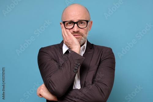 caucasian mature businessman being bored of financial problems isolated studio on blue background - fototapety na wymiar