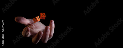 Two orange dice cubes thrown in the air above caucasian male hand against black Canvas Print