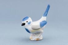 Porcelain Bird Figure On The Blue Background.