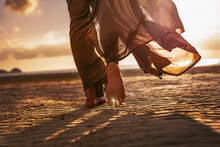 Close Up Of Woman Feet Walking Onthe Beach At Sunset