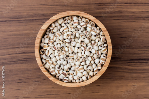 Fotografie, Tablou Close-up white Job's tears ( Adlay millet, pearl millet or coix seeds ) in wooden bowl and scoop isolated on wood table background