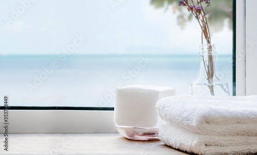 Fotografía Stack of clean bath towels on wooden table near the window with seascape