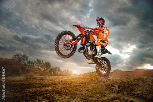Fototapeta Side View of the Professional Motorcycle Rider Driving on the mountains and Further Down the Off-Road Track