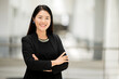 portrait Working woman Asian wearing a black suit, smiling, Crossed hands looking at the camera with confidence
