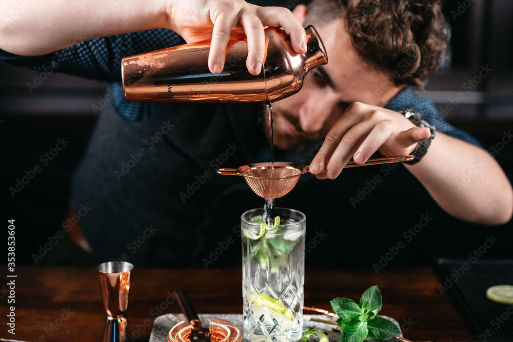 Fototapeta Expert bartender and barman pouring and preparing mojito cocktails
