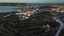Aerial View Of Golden And Warm Rising Sun Over Peniche's Peninsula Wide Open.