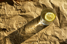 Water With Lemon On Crumpled P...