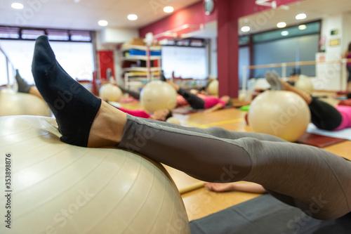 Photo Piernas de mujer apoyadas en balón de pilates
