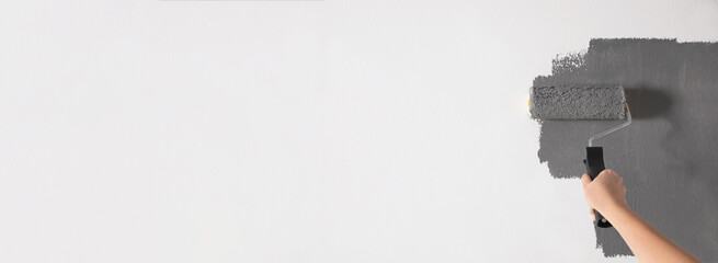 Professional decorator painting white wall with grey dye, space for text. Banner design