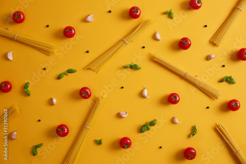 Obraz Raw ingredients for making pasta. Spaghetti, tomatoes, garlic and basil leaves. Herbs and spices for Italian food. Meal preparation. Yellow background. Cooking homemade delicious cuisine. Eating - fototapety do salonu
