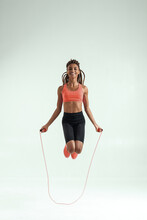 Healthy And Happy. Full Length Of Smiling Beautiful African Woman With Perfect Body Skipping Rope While Exercising In Studio Against Grey Background
