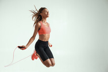 Flying. Happy And Young African Woman With Perfect Body Skipping Rope While Exercising In Studio Against Grey Background