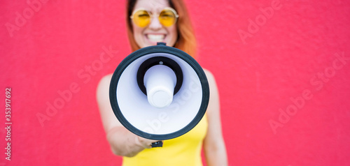 A woman in a dress with glasses and earrings stands in profile on a yellow background and shouts in a megaphone Wallpaper Mural