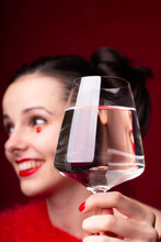 Beautiful Girl In Red Drinks Water From A Glass