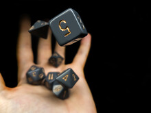 Hand Catching A Set Of Gray Dice On A Black Background
