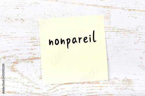 Photo Yellow sticky note on wooden wall with handwritten word nonpareil