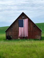 Rustic Old Barn With American Flag Hanging On The Side