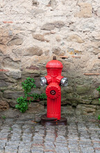 Red Fire Hydrant Against A Stone Wall