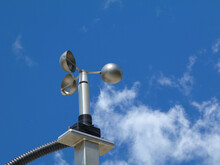 Anemometer Wind Speed Indicator Measuring Device Fixed To Aluminum Bracket On Tube Post. Meteorological Device. Abstract Low Angle View. Spoon Shaped Semi Sphere Blades. Clear Blue Sky. White Clouds