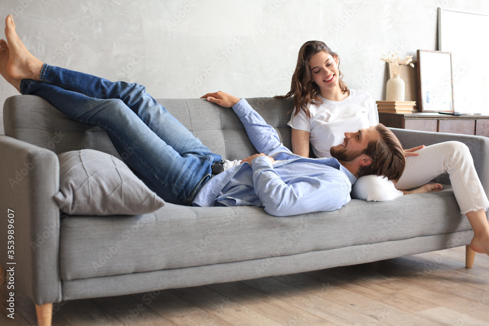 Fototapeta Young loving couple relaxing on sofa together, husband lying on wife legs resting on couch, concept of capture happy moment.