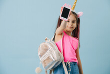 Happy Little Girl In A Pink Shirt Showing Phone Over Blue