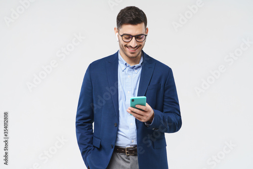 Young man dressed in blue blazer and shirt, wearing glasses, looking attentively Fototapeta