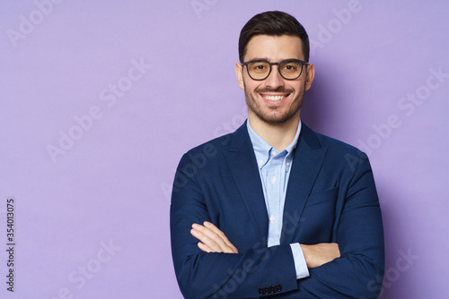 Business guy in glasses and formal clothes looking at viewer with confidence and friendly smile, standing with arms crossed, isolated on purple background, copyspace on left
