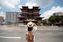 A Woman Tourist Is Traveling At Buddha Relic Temple With Singapore Urban City Skyline With Beautiful Landmark And Iconic View. (Chinese Means Buddha Relic Temple)