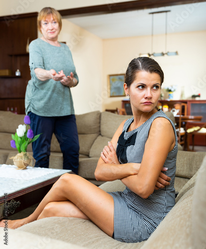 Fototapeta Elderly mother and adult daughter scandal in domestic interior