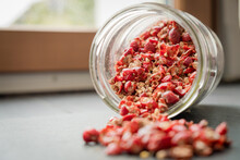 Wild Rose Hip Dry Fruit Spilled On The Black Rock Surface From Glass Jar