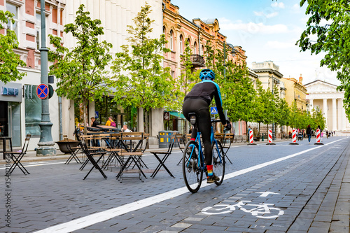 Rider cycling on the road bike in Vilnius city center reopening with open air restaurant and bar during Covid or Coronavirus emergency, sustainable transport concept #354028664