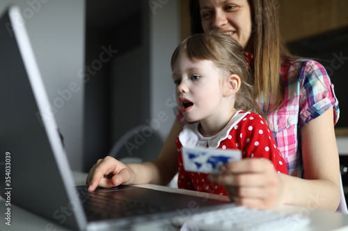Photo Woman with child at home enter credit card online