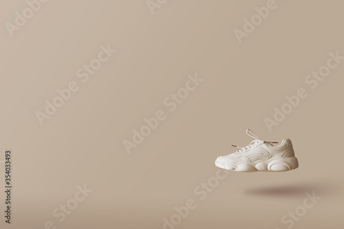 Photo Modern one female sneaker of light color flying on a beige background