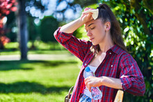 Young Unhappy Tired Woman With Cold Refreshing Water Suffering From Hot Weather While Walking In A Park