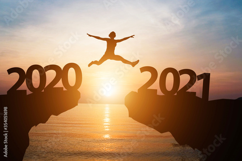 Fotografie, Tablou Man jump from year 2020 to 2021 with sunlight and sea