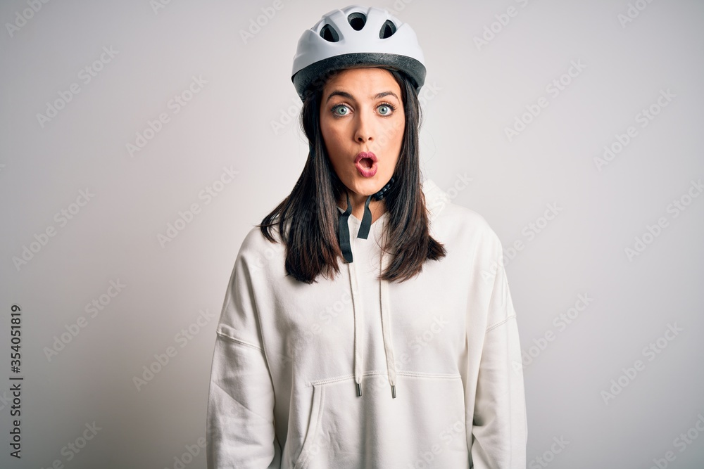 Fototapeta Young cyclist woman with blue eyes wearing bike helmet over isolated white background afraid and shocked with surprise expression, fear and excited face.