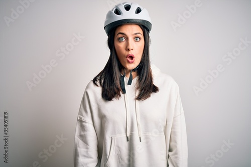 Photo Young cyclist woman with blue eyes wearing bike helmet over isolated white background afraid and shocked with surprise expression, fear and excited face