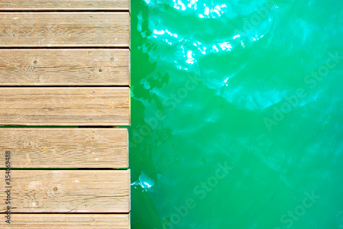 Canvastavla Summer background, wooden footbridge on swimming lake with turquoise water