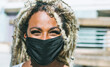 canvas print picture - Portrait of african girl with blond dreadlocks wearing face protective mask for Coronavirus prevention - Covid 19 lifestyle and trendy people concept - Focus on face