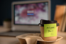 Back To Work Concept. Closeup Of Welcome Note On Takeaway Coffee Cup In Office Desk. Message From A Colleague Or Boss