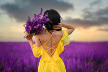 Summer Mood. A Woman In A Luxurious Yellow Dress Is Standing In A Purple Flowering Field With Her Back To The Camera. Close Up.