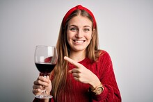 Young Beautiful Redhead Woman Drinking Glass Of Red Wine Over Isolated White Background Very Happy Pointing With Hand And Finger