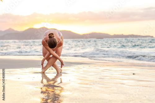 Fotografia Woman practices yoga at seashore