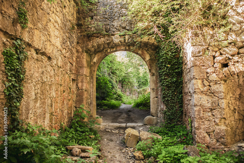 Photo Overgrown ruined, stone walls and arc doors of old, abandoned castle on the Tepe